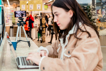 Young woman blogger at the mall working on a laptop, a tripod with a mobile phone are nearby