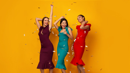 Three Girls Dancing Having Party With Confetti Over Yellow Background