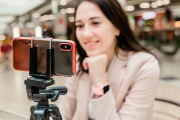 A young woman blogger in a mall works communicates on a mobile phone. Mobile phone on a tripod