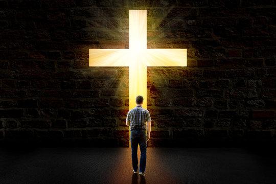 a man walking towards a glowing cross