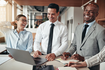 Diverse businesspeople laughing while working at an office table