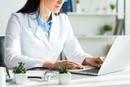 cropped view of doctor having online consultation with patient on laptop in clinic office