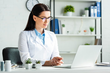 confident doctor having online consultation with patient on laptop in clinic office
