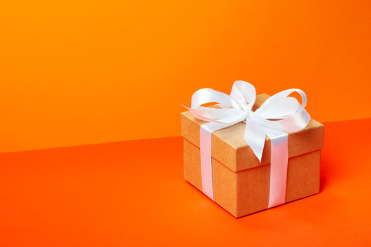 Trendy attractive minimalistic gift on the orange background. Merry Christmas, St. Valentine's Day, Happy Birthday and other holidays concept. Copy space.
