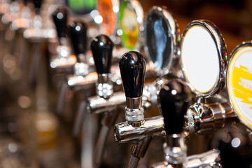 Row of Beer Taps in Bar for different types of drink. Bar interior