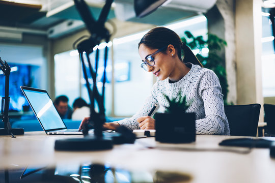 Professional female manager writing statement browsing information on laptop computer, woman employee working in office planning business project using netbook application for accountings