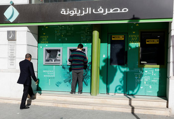 A man uses an ATM cash machine in downtown Tunis, Tunisia