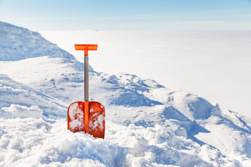Shovel for  snow cleaning during snowfall or avalanche. Snow storm in winter time season. Tool for maintenance during drive away.