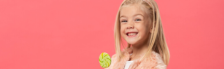 panoramic shot of smiling and cute kid holding lollipop isolated on pink