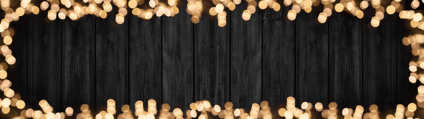 Festive celebration silvester background panorama banner long - Frame made of golden yellow bokeh lights with golden firework glitter isolated on dark black rustic wooden texture, with space for text Wall mural