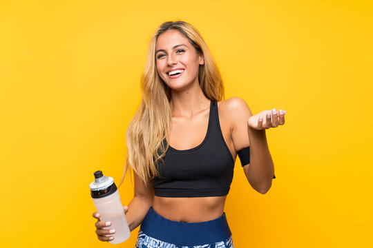 Young sport woman with a bottle of water over isolated background