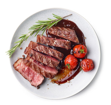 Grilled sliced Beef Steak with sauce, tomatoes and rosemary on a white plate Isolated on white background top view
