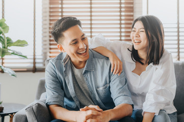 Asian couple having fun and laughing in loving room
