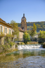 Small waterfall on the river Cuisance in the French town of Arbois, France with church tower in background.