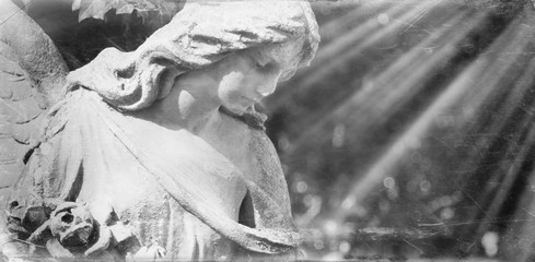 Vintage image of a sad angel on a cemetery against the background of leaves. Retro styled picture.
