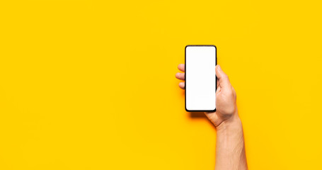 Male hands hold a modern black smartphone with white blank screen on yellow background. Modern technology, phone, gadget in hands, touch screen, template for your design. Mockup