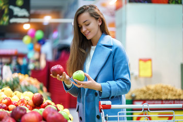 Portrait of attractive woman buyer with cart in the grocery shop during choosing and buying fresh apples at fruit department