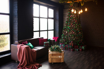 Dark loft interior. Christmas tree with a bunch of boxes with gifts. A beautiful green leather sofa on the background of a gray brick wall with panoramic window.
