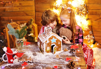 two small children-a boy with curly hair and a red-haired girl prepare a gingerbread house and have fun against the background of Christmas lights and decor.Christmas tradition