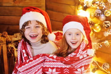two cute funny little children in Santa hats-a boy and a girl having fun wrapped in a cozy warm red plaid with Scandinavian arnament on the background of Christmas decor.