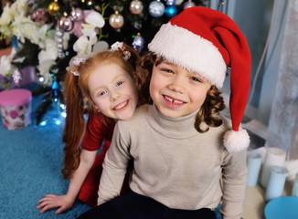 small children - a boy with curly hair in a Santa hat and a girl with red hair smiling and hugging on the background of a Christmas tree.