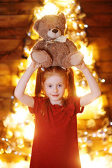 a little girl with red hair holding a Teddy bear on a wooden background and on the background of a Christmas tree and decor