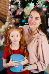 mother with a little daughter with red hair with a box with a gift in her hands smiling and hugging on the background of the Christmas tree
