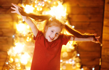 little cute girl with red hair smiling and having fun on wooden background and on Christmas lights background and decor.