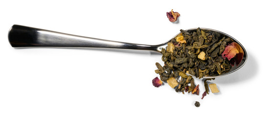 Spoon and green tea with aromatic additives on a white background