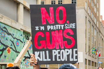 A protester holds sign NO GUNS at the March for Our Lives rally