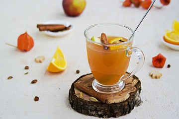 Apple cider with spices. Alcoholic or non-alcoholic hot drink made from fresh unfiltered apple juice with spices, apple slices and orange in a glass mug on a light concrete background.