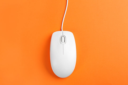 Modern wired optical mouse on orange background, top view