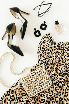 Fashion composition with female clothes and accessories. Leopard print dress, high-heel shoes, earrings, glasses, purse, perfume on white background. Flat lay, top view minimal beauty look.