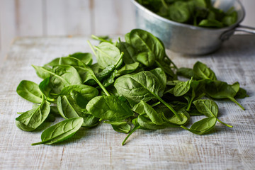 Fresh spinach leaves on wood, colander