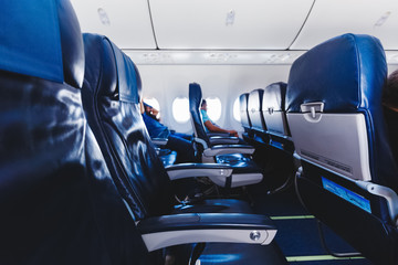 Plane interior in blue colors. Indoor of airplane seats and passengers.
