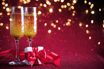 Two glasses of champagne with gift on red background