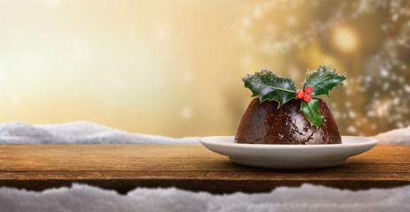 Christmas banner background of a traditional Christmas pudding on the right with a sprig of holly...