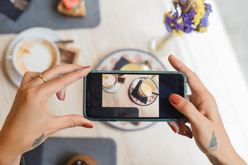 Overhead view of woman in a cafe taking cell phone picture of coffee