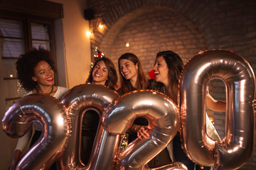 Girlfriends at New Year party holding balloons 2020