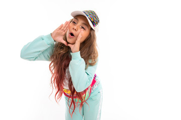 Little pretty caucasian girl in a tracksuit screams to someone, picture isolated on white background