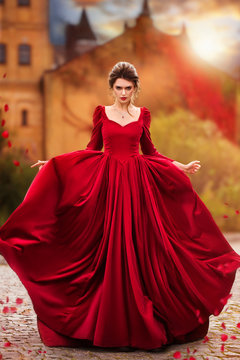 Beautiful girl in a burgundy red dress walking near old castle on a background of autumn grape leaves in the park, October. Radomyshl