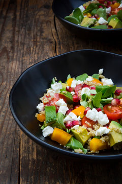 Salad bowl with lamb's lettuce, quinoa, yellow bell pepper, cocktail tomato, avocado, feta and pomegranate seeds