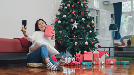 Asian women celebrate Christmas festival. Female teen relax happy holding Gift and using smartphone selfie with Christmas tree enjoy xmas winter holidays in living room at home.
