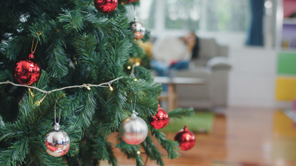 Close up of christmas tree and christmas decorations in living room at home.