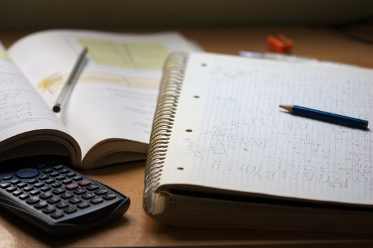 A notebook with math exercises written in pencil next to a calculator