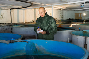 Man inspecting tanks for rearing trout fry