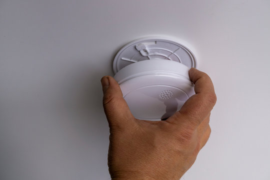 Handyman installing a smoke detector on the ceiling