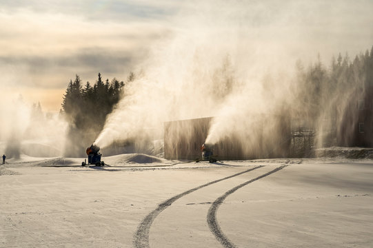 Snow cannon in winter mountains. Snow-gun spraying artificial ice crystals. Machine making snow.