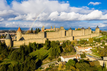 Rainbow over Cite de Carcassonne, a medieval hill-top citadel in the French city of Carcassonne, fortified by two castle walls. Aude, Occitanie, France. Aerial view. Pyrenees mountains background