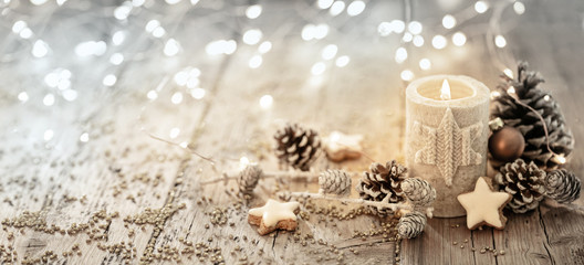 White Christmas candle on rustic wooden boards -  Decoration with natural elements, twigs, pine...